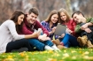 Group of young people using digital tablet and smart phone outdoors.